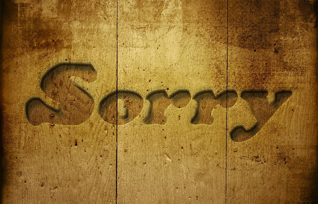 The word sorry etched into what looks like a kitchen table